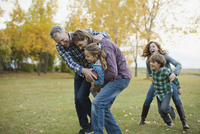 Multi-generation family playing American football in park