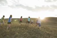 Rear view of playful schoolchildren running on field 11096041844| 写真素材・ストックフォト・画像・イラスト素材|アマナイメージズ