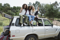 Portrait smiling young women gesturing peace sign on top of car