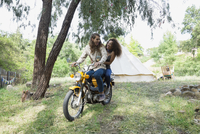 Young couple writing motorcycle outside camping yurt