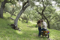 Affectionate young couple on motorcycle in woods