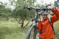 Mature man carrying mountain bike