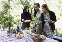 Women setting patio table for dinner party