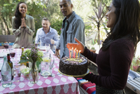 Woman serving birthday cake at patio table
