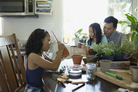 Father and daughters painting flowerpots at kitchen table