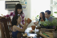 Family painting flowerpots at kitchen table