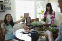 Family painting flowerpots at kitchen table 11096042114| 写真素材・ストックフォト・画像・イラスト素材|アマナイメージズ