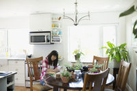 Woman drying herbs at kitchen table