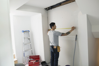 Man measuring and marking wall for home improvement project