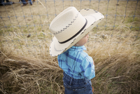 Toddler boy in cowboy hat at fence on ranch