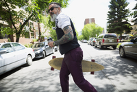 Hipster man with tattoos and coffee holding skateboard crossing street