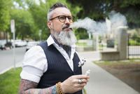 Cool hipster with gray beard and tattoos smoking cigarette on urban sidewalk