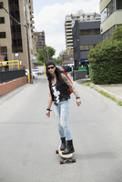 Cool mature woman skateboarding in urban alley