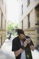 Cool man with mohawk smoking cigarette in urban alley