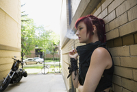 Cool woman with red hair smoking cigarette in urban alley