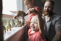 Happy father and children playing with toy dinosaurs at windowsill