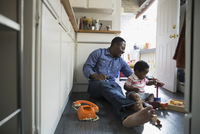 Father and son playing with toys on kitchen floor