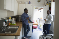 Men drinking beer talking in kitchen