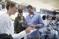 Saleswoman with clipboard helping couple with digital tablet in home gym equipment store