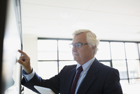 Senior businessman using touch screen television in conference room