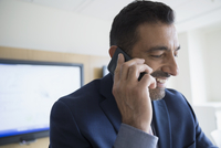 Close up smiling businessman talking on cell phone