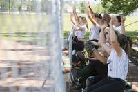 Middle school girl softball team cheering on bench