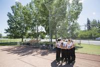 Middle school girl softball team in huddle on baseball diamond