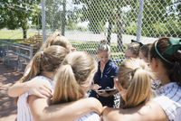 Coach and middle school girl softball team in huddle on baseball diamond