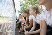 Focused middle school girl softball team watching game on bench