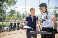 Coach with clipboard preparing middle school girl softball player in batter