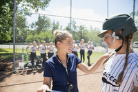Coach talking to middle school girl softball player in batter