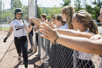 Middle school girl softball team high fiving teammate over fence