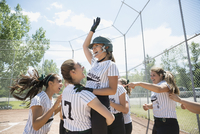 Enthusiastic middle school girl softball team celebrating on baseball diamond