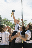 Middle school girl softball team celebrating lifting teammate holding trophy