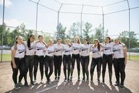 Portrait middle school girl softball team in a row on baseball diamond