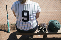 Middle school girl softball player sitting on bench next to baseball glove and helmet 11096043482| 写真素材・ストックフォト・画像・イラスト素材|アマナイメージズ