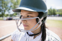 Close up serious middle school girl softball player wearing batting helmet