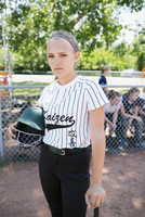 Portrait confident middle school girl softball player holding batting helmet