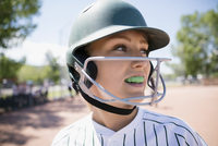 Close up middle school girl softball player with mouth guard wearing batting helmet