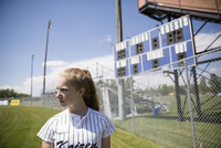 Serious middle school girl softball player looking away on sunny field