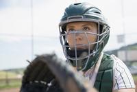 Focused middle school girl softball catcher wearing helmet