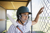 Serious middle school girl softball player wearing batting helmet and holding bat in dugout 11096043522| 写真素材・ストックフォト・画像・イラスト素材|アマナイメージズ