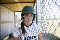Portrait serious middle school girl softball player wearing batting helmet and holding bat in dugout 11096043523| 写真素材・ストックフォト・画像・イラスト素材|アマナイメージズ