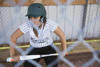 Serious middle school girl softball player wearing batting helmet and holding bat in dugout 11096043524| 写真素材・ストックフォト・画像・イラスト素材|アマナイメージズ