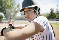 Serious middle school girl softball player wearing batting helmet watching game