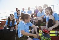 Middle school girl soccer team talking and preparing on bleachers 11096043530| 写真素材・ストックフォト・画像・イラスト素材|アマナイメージズ