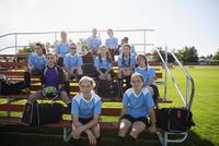 Portrait confident middle school girl soccer team on bleachers 11096043532| 写真素材・ストックフォト・画像・イラスト素材|アマナイメージズ