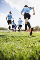 Middle school girl soccer team running onto sunny field 11096043540| 写真素材・ストックフォト・画像・イラスト素材|アマナイメージズ
