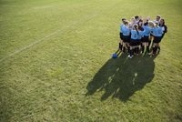 Middle school girl soccer team huddling with coach on sunny field