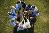 Overhead view middle school girl soccer team joining hands with coach in huddle on field 11096043556| 写真素材・ストックフォト・画像・イラスト素材|アマナイメージズ